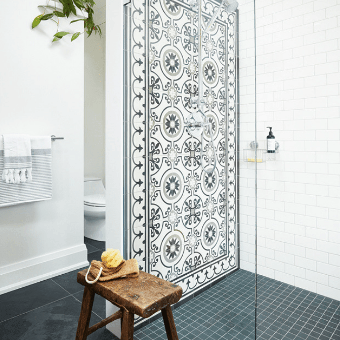 Large glass bathroom shower stall with blue patterned feature wall tiles
