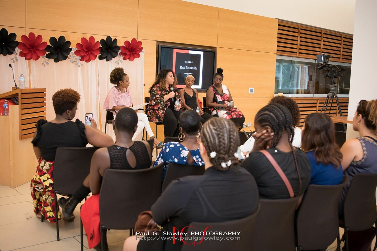Four Black female panelists sit on a stage speaking to an audience of women